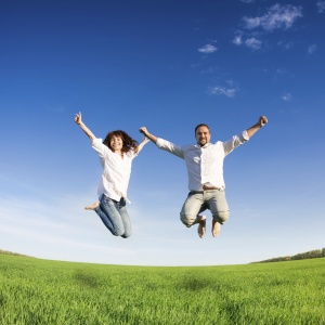 Happy couple jumping in green field against blue sky. Summer vacation concept